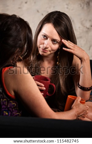 Concerned lady with hand on head listening to friend - stock photo
