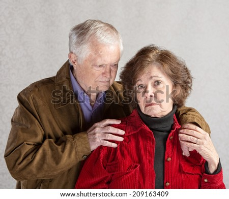 Concerned mature husband comforting depressed senior wife - stock photo