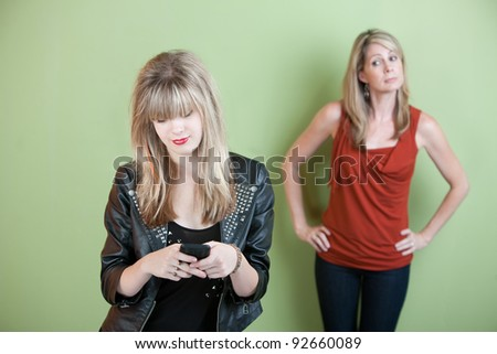 Concerned mom watches teen send text messages on phone - stock photo