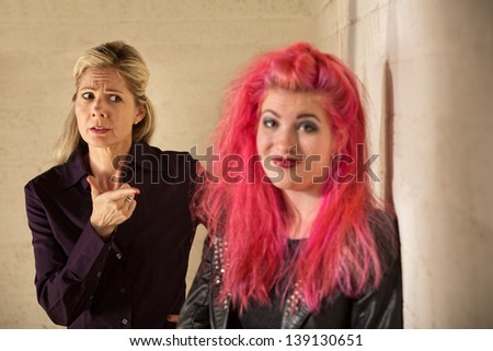 Concerned mother pointing at grinning daughter in pink hair - stock photo