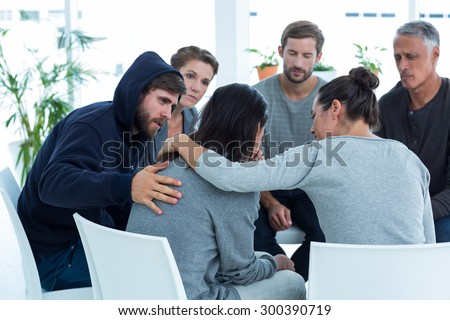 Concerned patients comforting another in rehab group at a therapy session