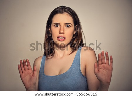 Concerned scared woman dodging something arms raised trying to avoid unpleasant situation isolated on gray wall background   - stock photo