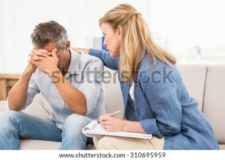 Concerned therapist comforting male patient in the office - stock photo