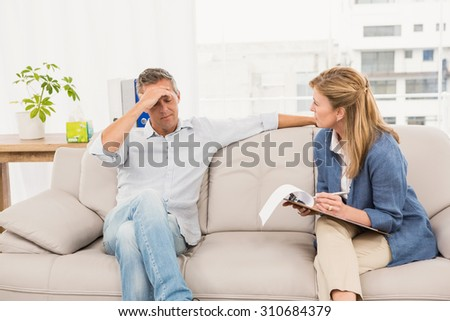 Concerned therapist talking with male patient in the office