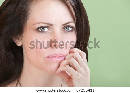 Concerned young Caucasian woman on green background with fingers to chin - stock photo