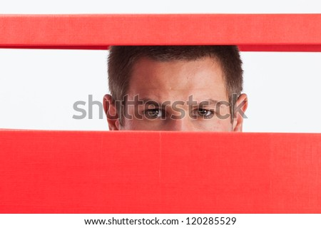 Concerned young man stuck in red box - stock photo