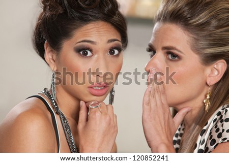 Concerned young woman listening to someone whispering secrets - stock photo