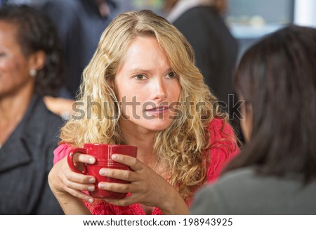 Concerned young woman talking with friend in cafe - stock photo