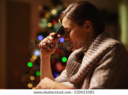 Concerned young woman with mobile phone in front of christmas tree - stock photo