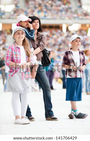 Concert at the stadium. Spectators are on the pitch. Family with three children close up - stock photo
