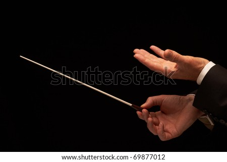 Concert conductor hands with baton isolated on black background