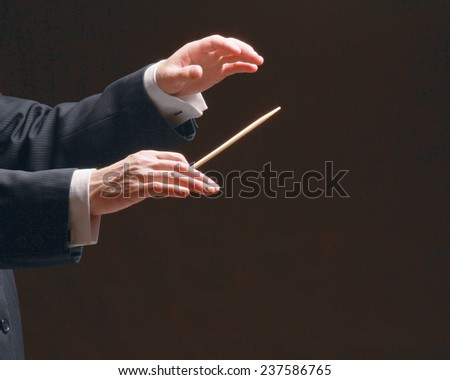 Concert conductor's hands with a baton, isolated on a black background - stock photo