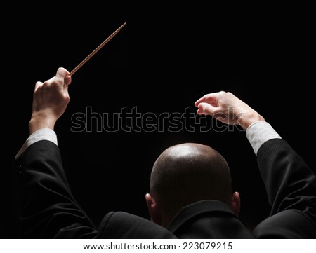 Concert conductor with a baton - stock photo