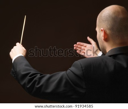 Concert conductor with baton isolated on black background, back-view