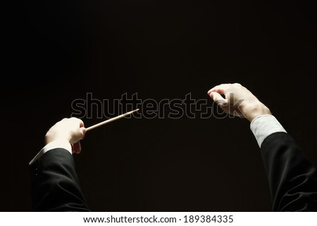Concert conductorwith a baton isolated on a black background, back-view