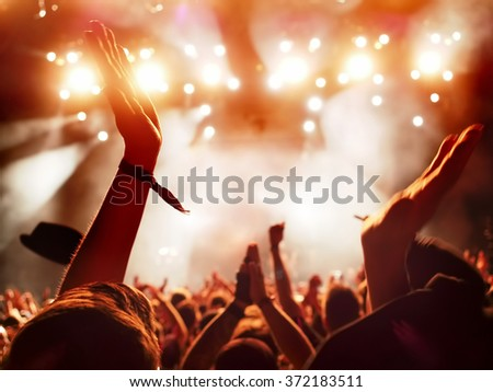concert crowd clapping at rock concert - slight motion blur of clapping hands - stock photo