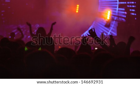 Concert Crowd in front of stage-lights raising hands.