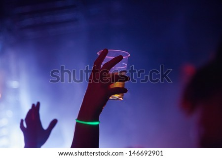 Concert Crowd in front of violet stage-lights - stock photo
