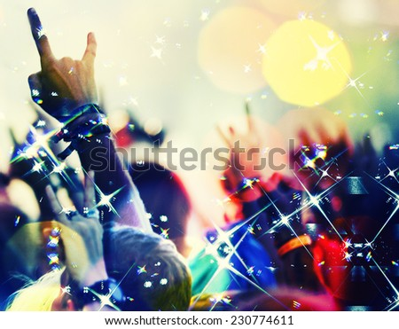 concert crowd in front  with hands up with rock-n-roll sign - stock photo