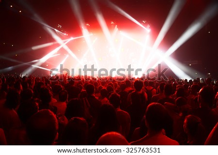 concert crowd of young people in front of bright stage lights - stock photo
