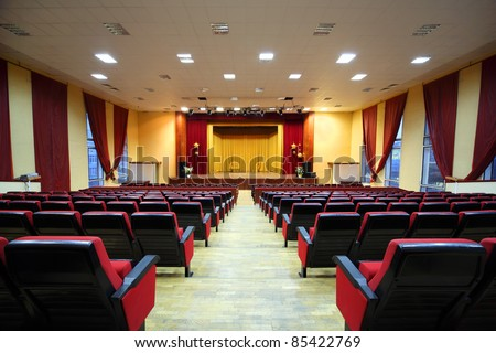 Concert hall and empty stage, many rows of red seats and stage