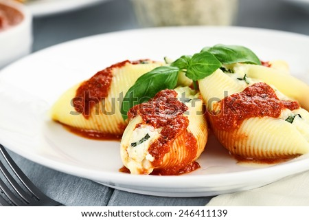 Conchigliei pasta stuffed with a ricotta cheese, mozzarella and basil leaves with extreme shallow depth of field. - stock photo