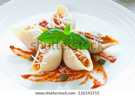 Conchiglioni pasta stuffed with salmon in tomato sauce - stock photo