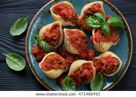 Conchiglioni stuffed with mincemeat and baked in tomato sauce, close-up, view from above