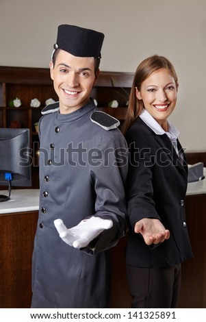 Concierge and receptionist in hotel offering welcome to guests - stock photo