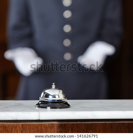 Concierge with white gloves pointing to hotel bell on counter - stock photo