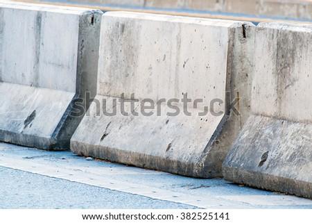 concrete barrier on the asphalt road - stock photo