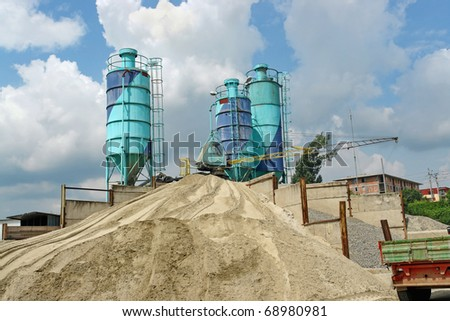 Concrete batching plant with three silos, heap of sand and gravel - stock photo