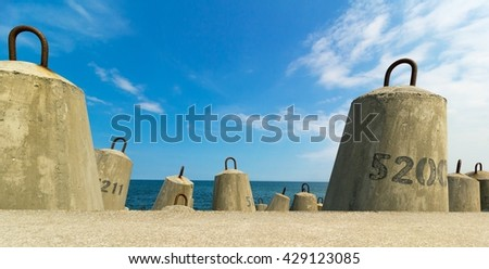 concrete block breakwater and baltic sea and blue sky - stock photo