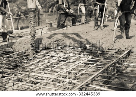 concrete casting work. using a concrete pump machine to fill the floor concrete with  worker or activities of labour team. sepia color tone for old feel selection focus to tube. - stock photo