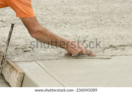 Concrete construction contractor installing a expansion joint in a sidewalk, curb and storm drainage gutter on a new urban road street project - stock photo