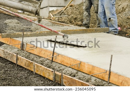 Concrete construction contractor using a float to  smooth a sidewalk, curb and storm drainage gutter on a new urban road street project - stock photo