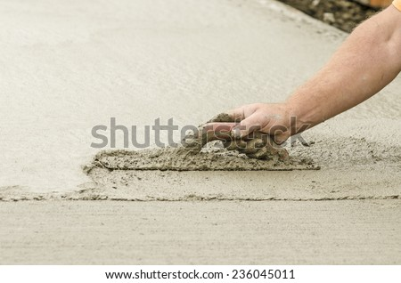 Concrete construction contractor using a trowel to smooth a sidewalk, curb and storm drainage gutter on a new urban road street project - stock photo