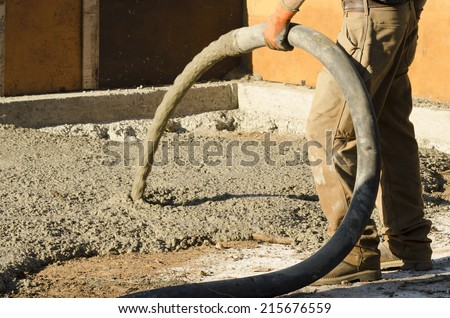 Concrete contractor using a concrete pump to fill the foundation of a custom luxury home - stock photo