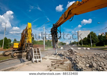 Concrete Crusher and Hydraulic Crushing Hammer demolishing reinforced concrete structures - stock photo