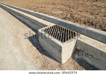 Concrete curb and drainage well at road construction site. The road is ready to be asphalted