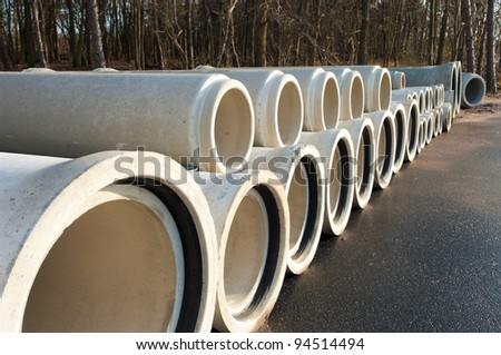 concrete drainage pipes on a newly built industrial area - stock photo
