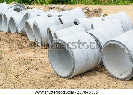 Concrete drainage pipes stacked for construction, irrigation, industry. - stock photo