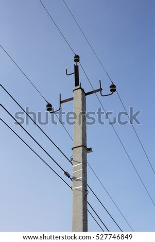 Concrete electric pole with wires against the sky