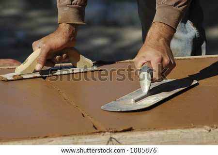 Concrete finisher with a trowel in each hand. - stock photo
