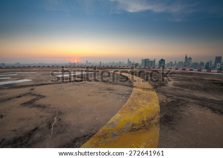Concrete floor of skyscraper rooftop building with yellow line lead to city sunset view