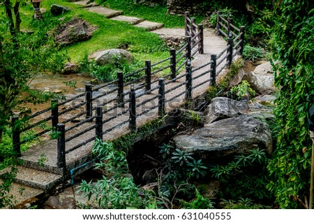 Concrete footbridge with artificial branch railing