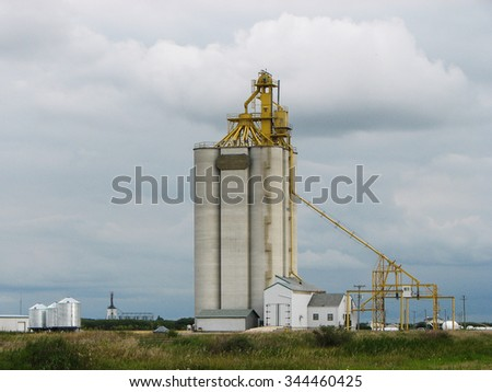 Concrete Grain Elevator with Cloudy Sky on Prairie