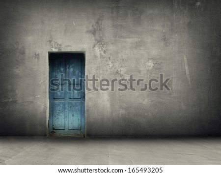 concrete grey wall and floor and blue vintage door with shadows