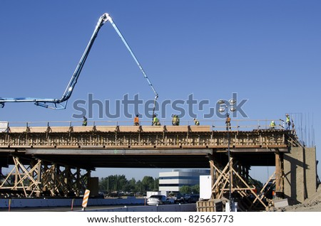 Concrete is pumped into wooden forms with an articulated boom for a bridge construction project - stock photo