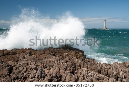 Concrete lighthouse beacon in the stormy sea - stock photo